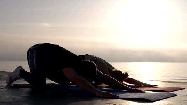 caucasian man and woman practicing yoga or stretching after workout in front the sea or ocean on the yoga mat. morning sunligth on the background - materassino ginnico video stock e b–roll