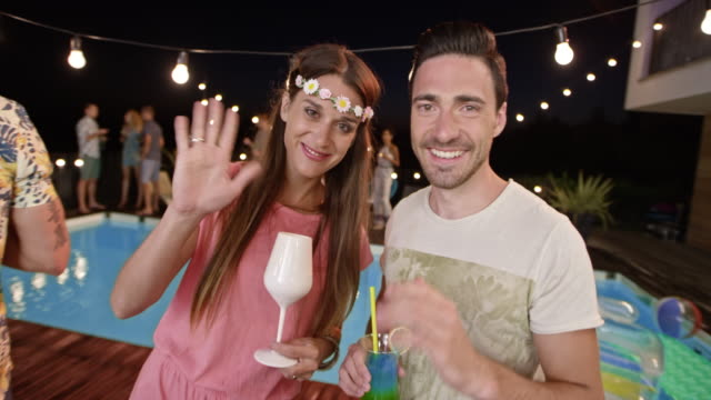 Caucasian man and woman talking at an evening party by the pool and waving into the camera for a smartphone video their friend is making