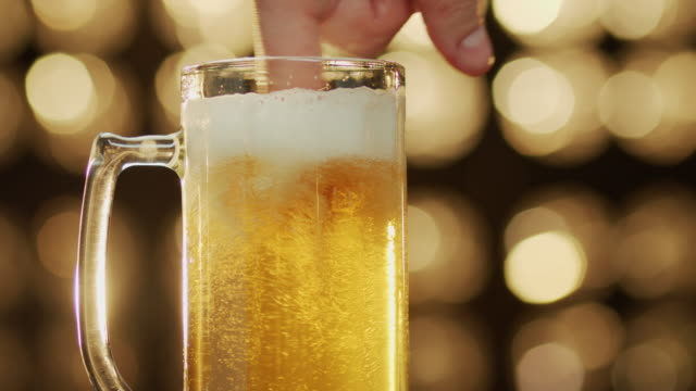 Caucasian man blend foam with a finger in a beer glass bokeh background close-up Caucasian man blend foam with a finger in a beer glass at bokeh background close-up. household fixture stock videos & royalty-free footage