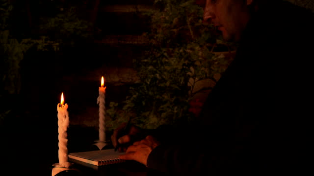 Caucasian man businessman or student sitting at the table at night. Candlelight illuminate notebook. Man write to notebook with pen by hand. Night dark warm atmosphere. Man blow candles and go out. video