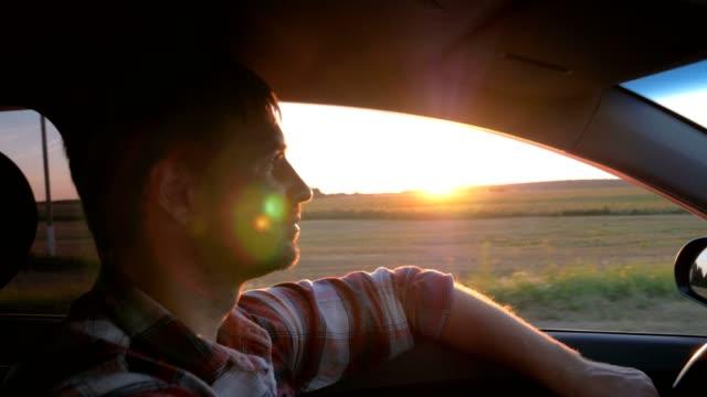 caucasian man drive in the car on the background of the sunset - opalenizna filmów i materiałów b-roll