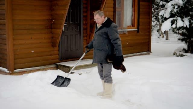 kaukasiska man knappast rensar en spade yard av snö på vintern efter snowstorm - skyffel bildbanksvideor och videomaterial från bakom kulisserna