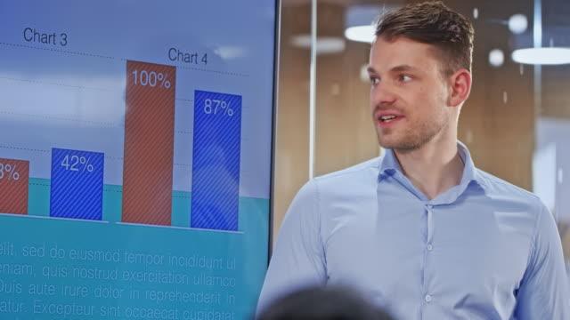 caucasian man holding a presentation in the glass conference room - продвижение трудовые отношения стоковые видео и кадры b-roll