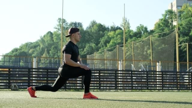 vídeos de stock e filmes b-roll de caucasian man in black sportswear and cap exercising. runner man warming up - campeão desportivo