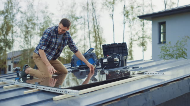vídeos de stock e filmes b-roll de caucasian man in checkered shirt is installing black reflective solar panels to a metal basis with a drill. he works on a house roof on a sunny day. concept of ecological renewable energy at home. - solar panel