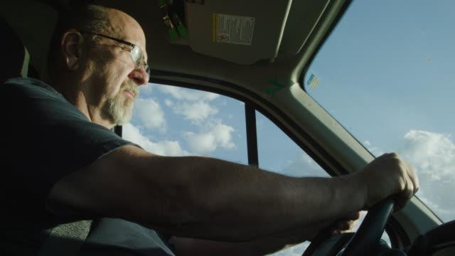 vídeos y material grabado en eventos de stock de un hombre caucásico en sus cincuenta conduce un camión en un día soleado al amanecer / puesta del sol - conductor de autobús
