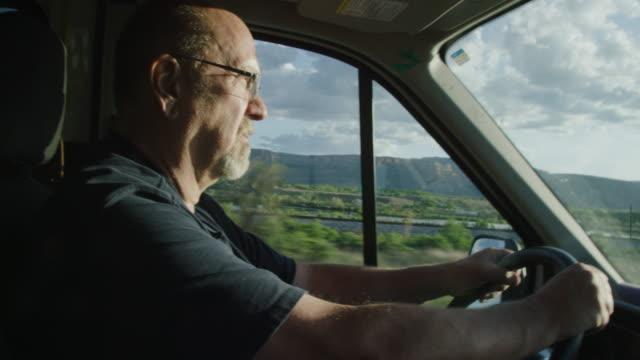 vídeos y material grabado en eventos de stock de un hombre caucásico en sus cincuenta conduce un camión en un día soleado en el oeste de colorado al amanecer / puesta del sol - conductor de autobús