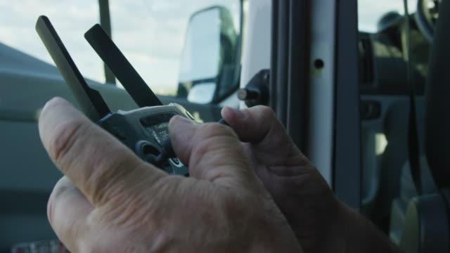 오십대의 백인 남성이 차량에 기대어 있는 동안 리모컨을 작동합니다. - 무인항공기 스톡 비디오 및 b-롤 화면