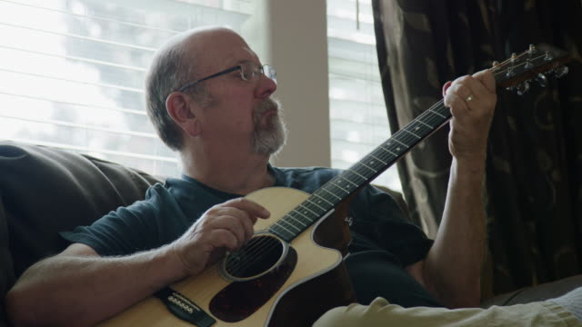 A Caucasian Man in His Fifties Plays an Acoustic Guitar in a Living Room A Caucasian Man in His Fifties Plays an Acoustic Guitar in a Living Room guitar stock videos & royalty-free footage