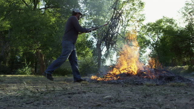 a caucasian man in his forties throws wooden sticks and branches on to a large flaming burn pile with a pitchfork outdoors - patyk część rośliny filmów i materiałów b-roll