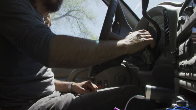 A Caucasian Man in His Forties with a Beard Opens His Car Door, Climbs in, Puts the Key in the Ignition, Starts the Car, Puts on His Seatbelt, and Puts the Car in Gear on a Sunny Day.
