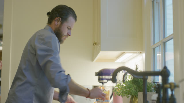 en kaukasisk man i fyrtioårsåldern med skägg fungerar på hans köksbänk inomhus - looking inside inside cabinet bildbanksvideor och videomaterial från bakom kulisserna