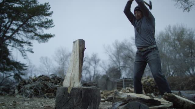 beyaz bir adam onun kırklı bir örgü şapka ve koruyucu gözlük ile ahşap bir günlük bulutlu bir günde alacakaranlıkta dışında ağaçlar tarafından çevrili bir balta ile yakacak odun için yarısında pirzola - şömine odunu stok videoları ve detay görüntü çekimi