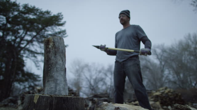 A Caucasian Man in His Forties with a Knit Hat and Safety Glasses Chops a Wooden Log in Half for Firewood with an Axe Surrounded by Trees Outside at Dusk on a Cloudy Day