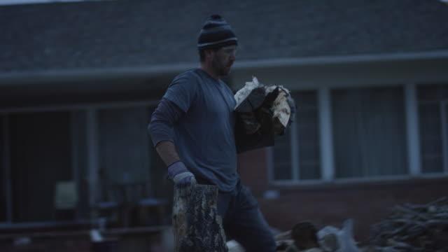 ein kaukasischer mann in den vierzigern mit strick mütze, schutzbrille und schutzhandschuhe stapel brennholz in einem holzstapel neben einem haus in der dämmerung - brennholz stock-videos und b-roll-filmmaterial