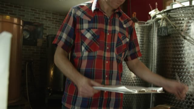 A Caucasian Man in His Thirties Records Information on a Clipboard in an Alcohol Distillery