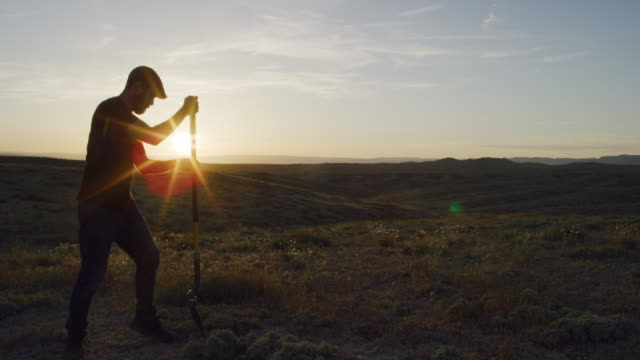 A Caucasian Man in His Thirties Wearing a Hat Digs a Hole in the Ground with a Shovel in the Desert at Sunset