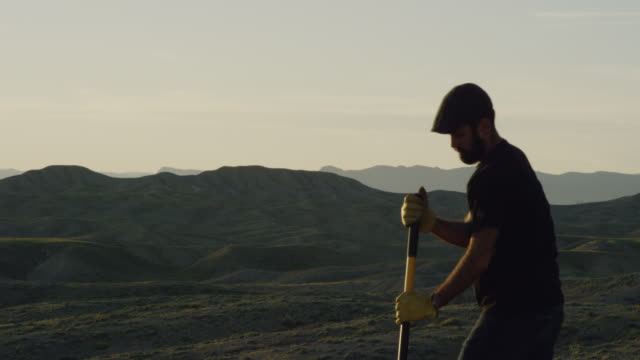A Caucasian Man in His Thirties with a Beard and Wearing a Hat and Work Gloves Digs a Hole in the Ground with a Shovel in the Desert at Sunset
