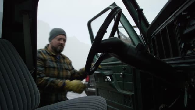 A Caucasian Man in His Thirties with a Beard Climbs into His Truck in the Mountains on a Snowy Winter Day