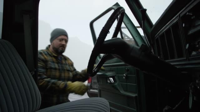 en kaukasisk man i trettioårsåldern med skägg klättrar in i sin lastbil i bergen på en snöig vinterdag - truck bildbanksvideor och videomaterial från bakom kulisserna