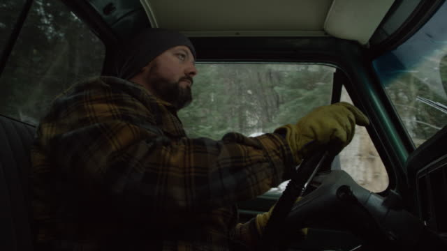 ひげを持つ 30 代の白人男は雪の降る冬の日の常緑林で彼のトラックをドライブします。 - あごヒゲ点の映像素材/bロール