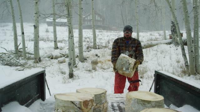 vídeos de stock, filmes e b-roll de um homem caucasiano em seus trinta anos, com uma barba coloca um log de aspen seu caminhão com a sua casa em segundo plano em um dia de inverno a neve nas montanhas - caminhonete pickup
