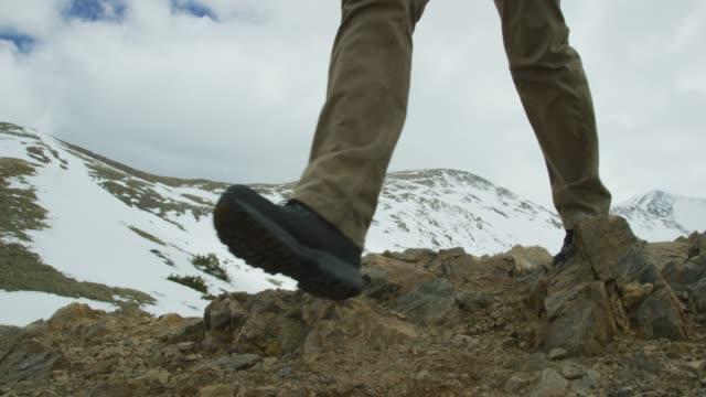 en kaukasisk man i tjugoårsåldern med skägg och en ryggsäck vandringar ett berg på loveland pass (continental divide) i rocky mountains i colorado under en overcast sky - klippiga bergen bildbanksvideor och videomaterial från bakom kulisserna