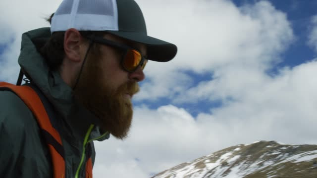 A Caucasian Man in His Twenties with a Beard and a Backpack Hikes a Mountain on Loveland Pass (Continental Divide) in the Rocky Mountains of Colorado under an Overcast Sky