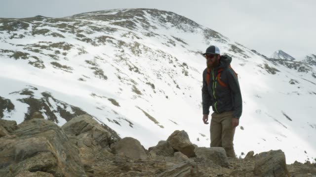 A Caucasian Man in His Twenties with a Beard and a Backpack Hikes a Mountain near Loveland Pass (Continental Divide) in the Rocky Mountains of Colorado under an Overcast Sky