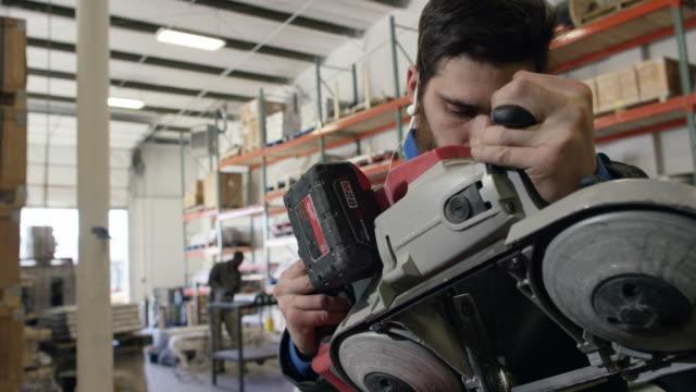 ein kaukasischer mann in seinen zwanzigern mit einem bart misst, markiert und schneidet ein stahlrohr mit einem handheld bandsäge in einer produktionsstätte - bandsäge stock-videos und b-roll-filmmaterial