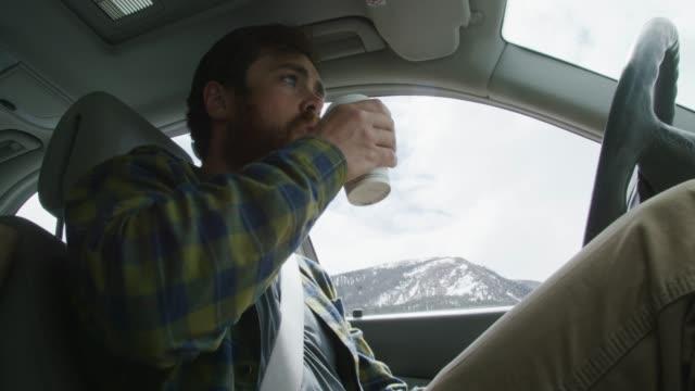 vídeos y material grabado en eventos de stock de un hombre caucásico en sus años veinte con barba coge una copa para ir, toma un sorbo, y lo vuelve a bajar en la consola mientras conduce a través de las montañas nevadas en invierno - café bebida