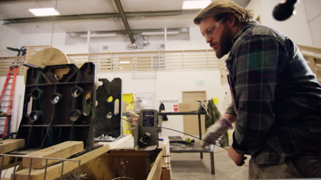Caucasian Man in His Twenties with a Beard Pulls Electrical Wire Through a Measuring Device (Length Counter) in a Manufacturing Facility Caucasian Man in His Twenties with a Beard Pulls Electrical Wire Through a Measuring Device (Length Counter) in a Manufacturing Facility manufacturing occupation stock videos & royalty-free footage