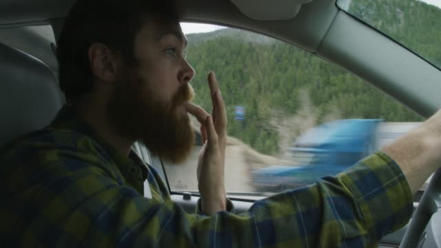 a caucasian man in his twenties with a beard shoves the rest of a sandwich into his mouth, licks his fingers, and wipes his hands on his bands while driving in the mountains with a forest - leccare video stock e b–roll