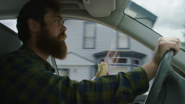 a caucasian man in his twenties with a beard takes bites out of a sandwich while driving through a mountain town on a sunny day - вредное питание стоковые видео и кадры b-roll