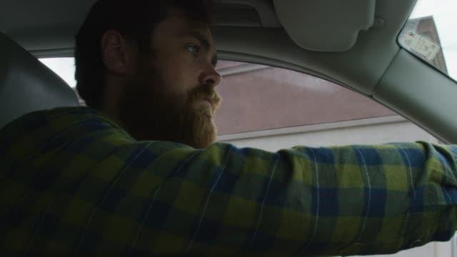 ein kaukasischer mann in seinen zwanzigern mit einem bart nimmt seine fast food bag, rollt sein autofenster hoch und treibt das auto an - schnellkost stock-videos und b-roll-filmmaterial