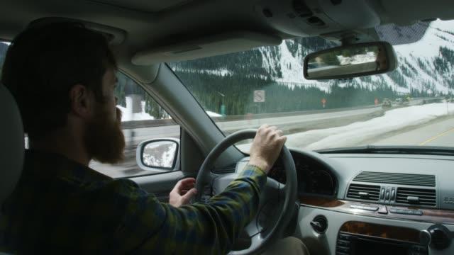 彼が冬に部分的に曇った空の下のコロラドのロッキー山脈の州間州70に沿って運転しているとき、彼がハンドルを持っているあごひげで20代の白人男性 - 冬点の映像素材/bロール