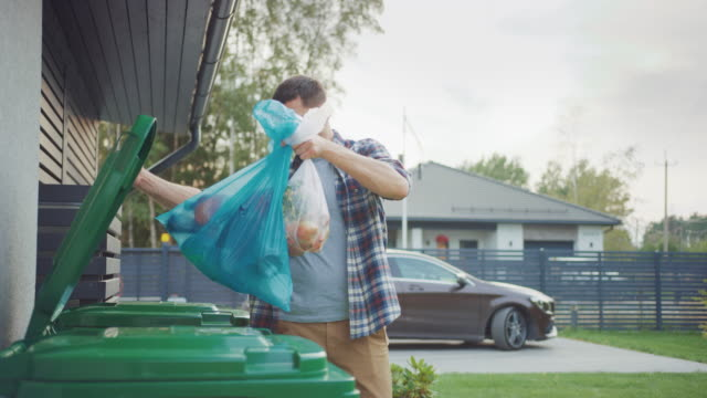 Caucasian Man is Walking Outside His House in Order to Take Out Two Plastic Bags of Trash. One Garbage Bag is Sorted into Biological Food Waste, Other is Thrown into Recyclable Bottles Garbage Bin.