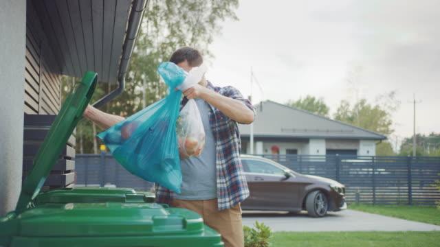 kaukasiska man går utanför sitt hus för att ta ut två plastpåsar med skräp. en soppåse sorteras i biologiskt matavfall, andra kastas i återvinningsbara flaskor soptunna. - food waste bildbanksvideor och videomaterial från bakom kulisserna