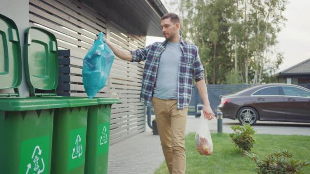 vidéos et rushes de l'homme caucasien marche à l'extérieur de sa maison afin de sortir deux sacs en plastique de la poubelle. un sac à ordures est trié dans les déchets alimentaires biologiques, l'autre est jeté dans des bouteilles recyclables poubelle. - lancer