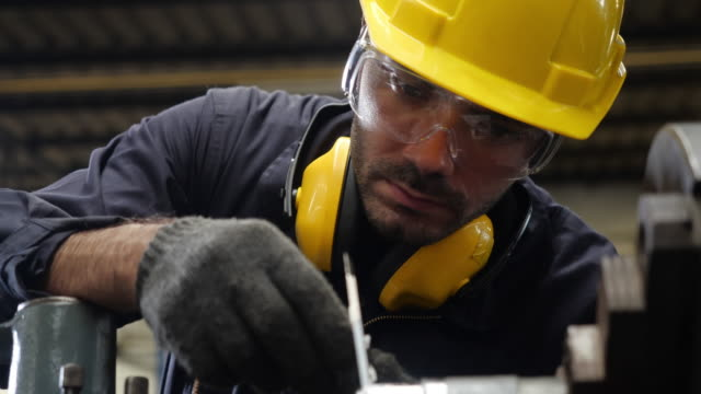 Caucasian man is working on a machine in an industrial factory.