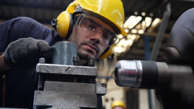 kaukasiska mannen arbetar på en maskin i en industrifabrik. - svarv bildbanksvideor och videomaterial från bakom kulisserna