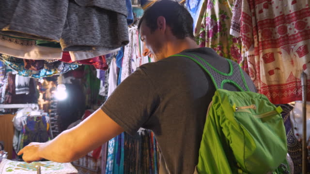 caucasian man looking for souvenirs in cambodian market - prodotto d'artigianato video stock e b–roll