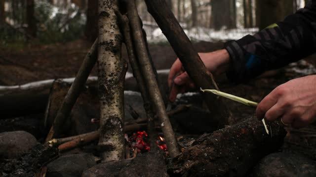 kar kaplı ormanda küçük şöminenin yanında bir sopa şiş yapan kafkas adam - bakir yer stok videoları ve detay görüntü çekimi