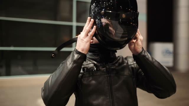 vídeos de stock e filmes b-roll de caucasian man motorcyclist wears a helmet on night street - helmet motorbike