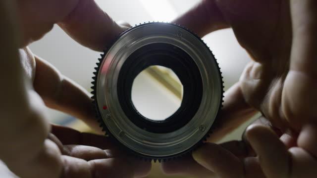 A Caucasian Man Opens and Closes a Lens Aperture