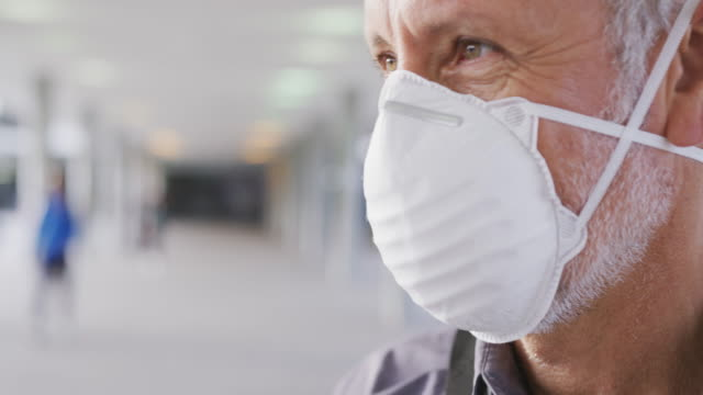 caucasian man out and about in the street wearing on a face mask against coronavirus - coprire video stock e b–roll