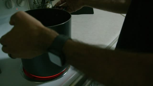 A Caucasian Man Places a Large Pot on to a Stop Top Range Set to High Heat in a Kitchen