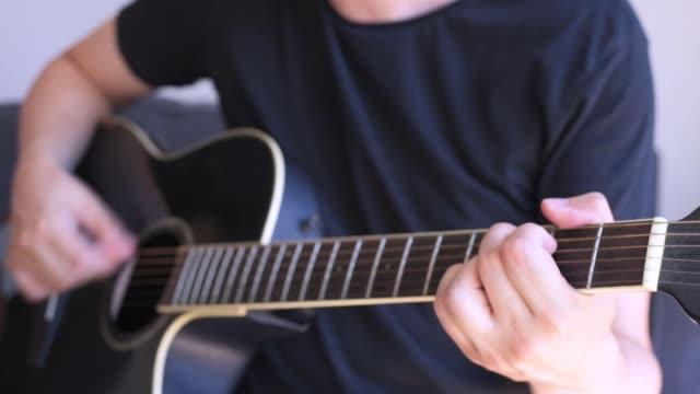 kaukasiska mannen spelar ackord i en svart akustisk gitarr. selektivt fokus på vänster hand - akustisk gitarr bildbanksvideor och videomaterial från bakom kulisserna