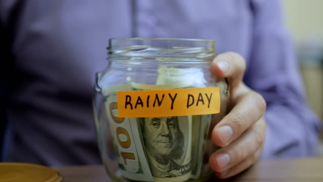 caucasian man putting a glass jar put in a drawer table with his savings for future rainy day - evento catastrofico video stock e b–roll