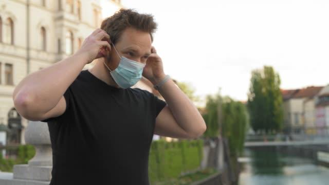 Kaukasische mens die op gezichtsmasker in de stad zet video
